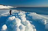 a photographer takes photos of washed up ice piles, along Lake Winnipeg, Manitoba, Canada