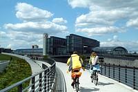 Two people cycling on bridge