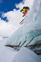 A backcountry skier airs off a crevasse in Mount Assiniboine, Mount Assiniboine Provincial Park, British Columbia, Canada
