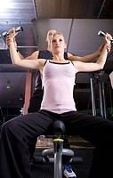 young woman training with dumbbells with help of trainer