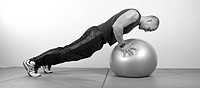 young man doing push_up on Swiss ball