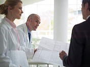 Architect discussing blueprint with doctors