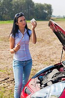 Young woman measuring the oil pressure in her car