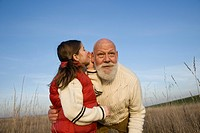 Girl whispering to her grandfather