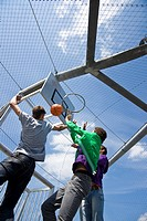 Boys playing basketball, low angle view