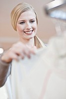 Young woman looking at clothes on a clothes rack, low angle view