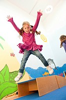 Children jumping over boxes, low angle view