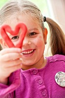 Little girl holding a self_made heart, portrait