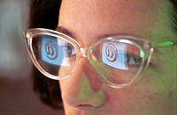 Portrait of a businesswoman with her computer screen reflecting in her glasses, France.