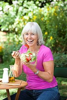 Woman eating salad in the open
