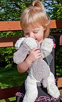 This precious shot image shows a Caucasian 2 year old girl kissing her favorite stuffed animal, a white and gray plush dog You can tell by her facial ...