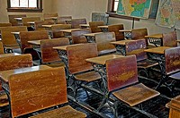 This photo is an vintage, turn of the century old school classroom with the wooden desks, wood floors, old radiator and vintage maps Full of rich trad...