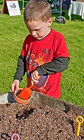 This 5 year old boy is a young gardener to be as he's planting a plan in a clay pot with shovels and a wheelbarrow full of potting soil He's got short...