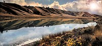 Barren hills with reflection in Shumway Lake, Kamloops, British Columbia, Canada