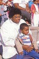 An African_American mother with her son listening to an assembly, St. Louis, MO