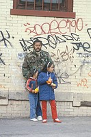 Latino man and daughters standing in front of graffiti covered walls, South Bronx, New York