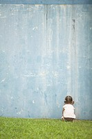 Girl crouching facing a wall, rear view