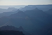 The Grand Canyon rises out of the blue haze at sunset.