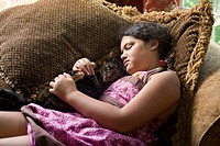 A young girls sleeps in a brown chair with her pet cat.