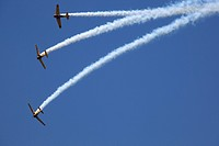 The Canadian Harvard Aerobatic Team form arcs of smoke at an airshow.