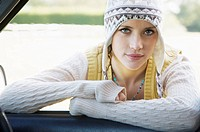 portrait of woman leaning into car smiling