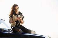 young woman sitting on the bonnet of jeep selecting music on her i pod