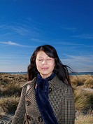 Asian Woman on beach with wind in hair