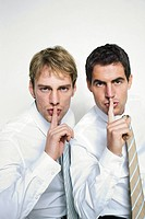 Two businessmen with finger on lips, portrait