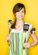 Young woman with apron and cooking utensils