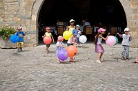 Children playing with balloons on Plaza Mayor, in Ainsa, Huesca, Spain in Pyrenees Mountains, an old walled town with hilltop views of Cinca and Ara R...