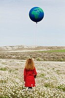 woman with globe balloon in field of flowers