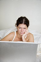 Woman with laptop in bed