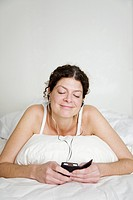Woman listening to music in bed