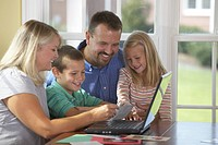 Family of 4 laughing and playing on the computer.