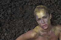 Portrait of young woman in gold body paint against rocky ground