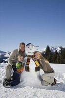 Portrait of family with snowman, smiling