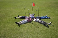 Mature men lying on backs around golf flag on golf course
