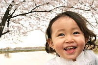 Portrait of a happy baby girl against cherry blossom tree