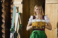 Portrait of mid adult woman holding pints of beer, smiling