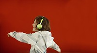Boy wearing headphones and dancing against red background