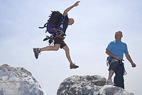 Mature man leaping over rocks at summit, side view