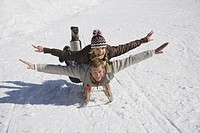 Couple sledding downhill with arms out, smiling