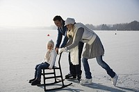 Parents pushing daughter on chair on ice, side view