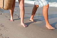 Legs of couple walking on beach