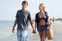 Teenage couple walking hand in hand on beach