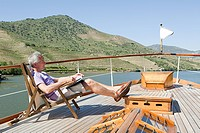 Senior man reading book on a boat holiday (thumbnail)