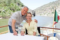 Senior couple with glasses of wine on a boat holiday (thumbnail)