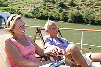 Senior couple sitting on deckchairs on a boat