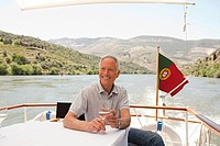 Senior man with a glass of wine on a boat holiday