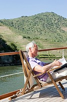Senior man reading book on a boat holiday
